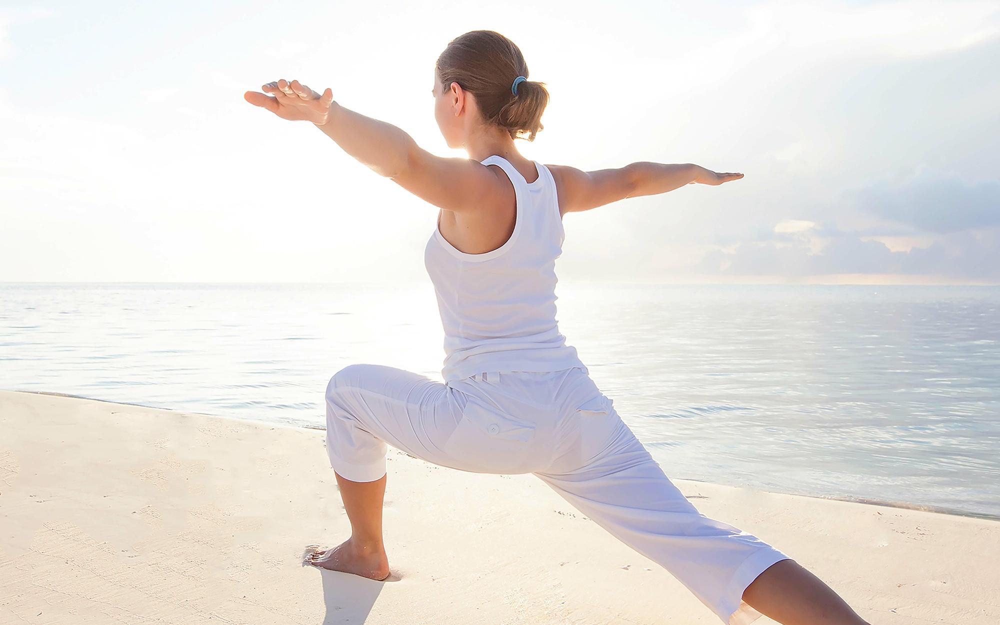 frau macht am strand yoga